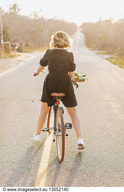 Young woman riding bicycle on rural road,  rear view,  Menemsha,  Martha's Vineyard,  Massachusetts,  USA