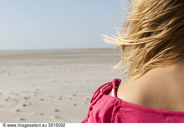 Young woman,  20-25 years,  on a windy day at the beach in St Peter Ording,  North Sea,  North Friesland,  Schleswig-Holstein,  northern Germany,  Germany,  Europe