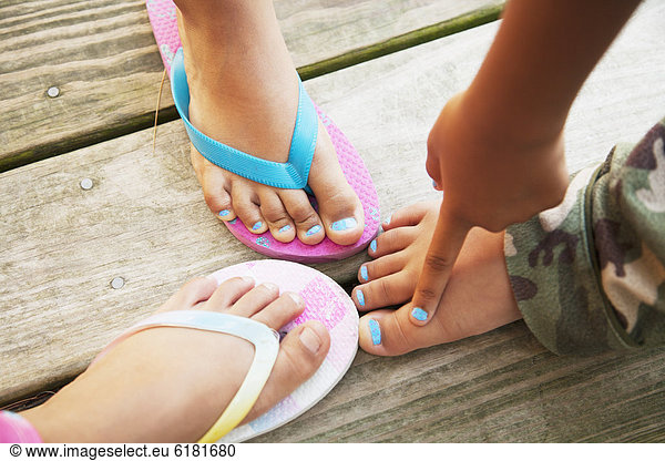 Hispanic children touching feet