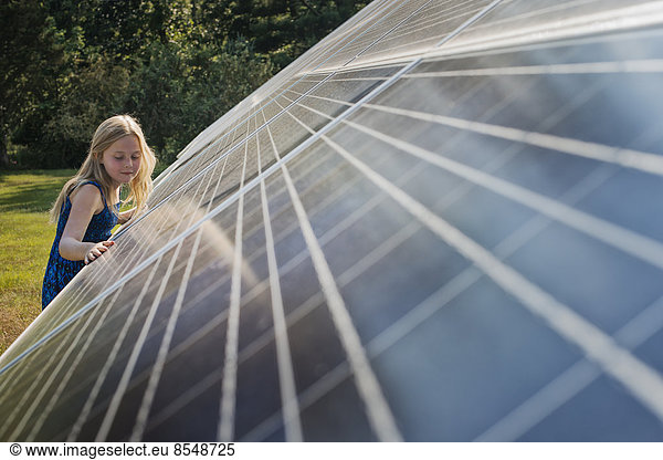 A young girl standing beside and leaning against a large solar panel installation.