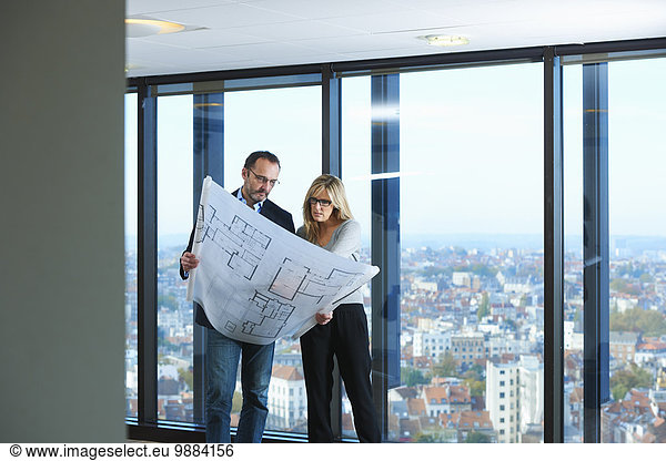 Two architects looking at plans in front of office window with Brussels cityscape,  Belgium