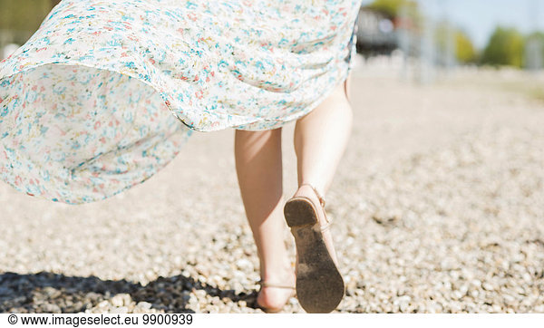 Woman walking on shingle beach