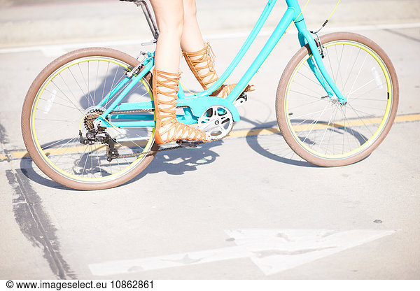 Legs and strappy sandals of young female cyclist at Venice Beach,  Los Angeles,  California,  USA