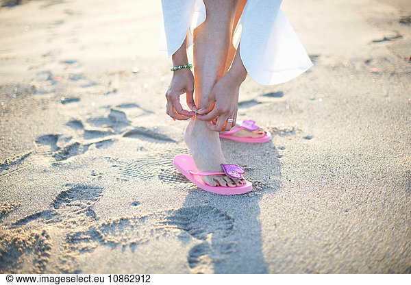 Cropped shot of woman fastening anklet on Santa Monica beach,  Cresent City,  California,  USA