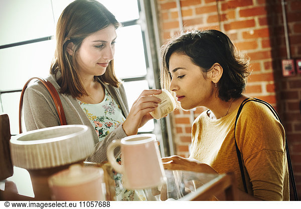 Two young women in a shop,  smelling a jar of lavender salve.