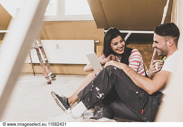 Young couple on construction site of their new home,  using digital tablet