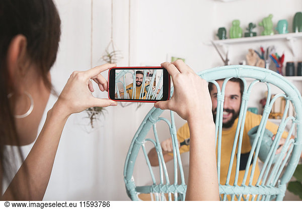 Young woman taking photo of bearded man painting wicker armchair at home