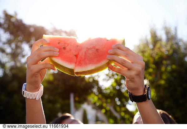 Teenage girls holding up watermelon in street
