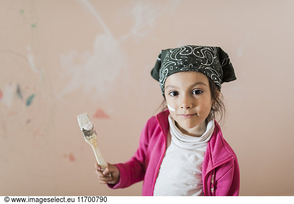 Portrait of little girl with paintbrush