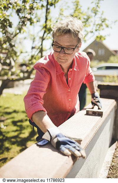 Senior women examining wooden plank on surrounding wall at yard