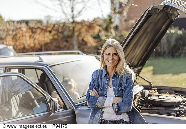 Smiling woman standing at vintage car
