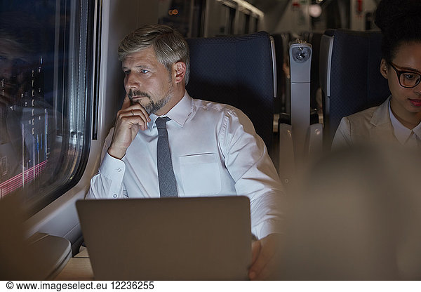Serious,  thoughtful businessman working at laptop,  looking out window on passenger train at night