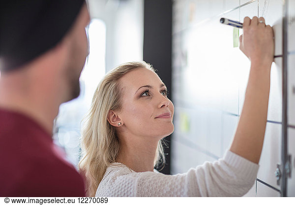 Male and female colleague planning ideas on office whiteboard,  over shoulder view