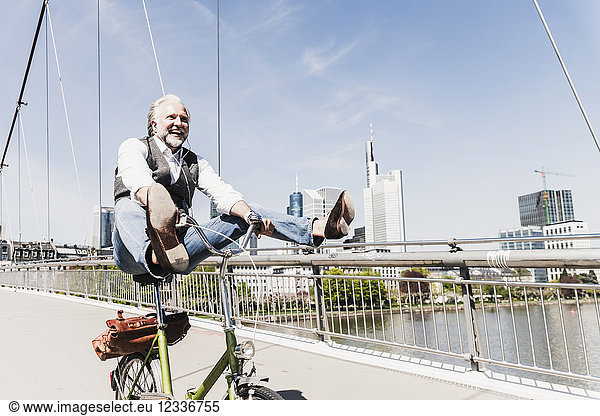 Playful mature man on bicycle on bridge in the city