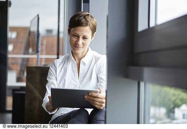 Businesswoman sitting in office at the window using tablet