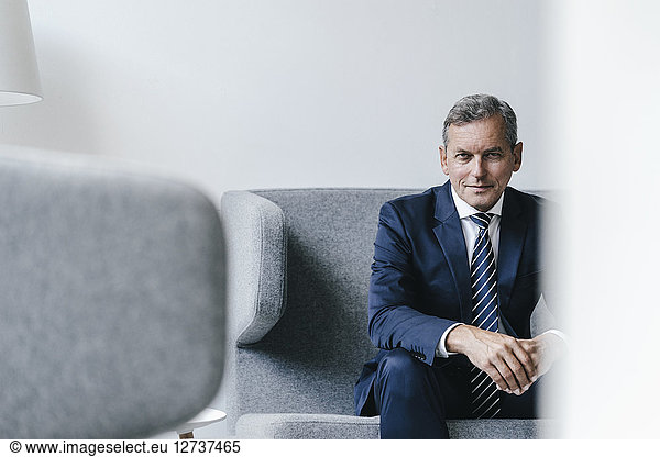 Portrait of mature businessman sitting on couch in his office