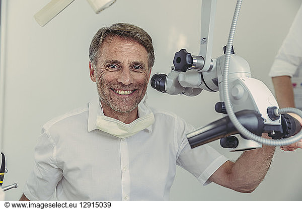 Dentist using microscope,  portrait