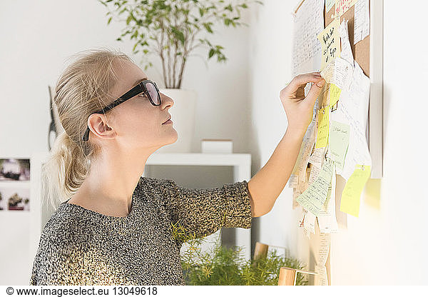 Businesswoman reading adhesive notes on bulletin board in creative office
