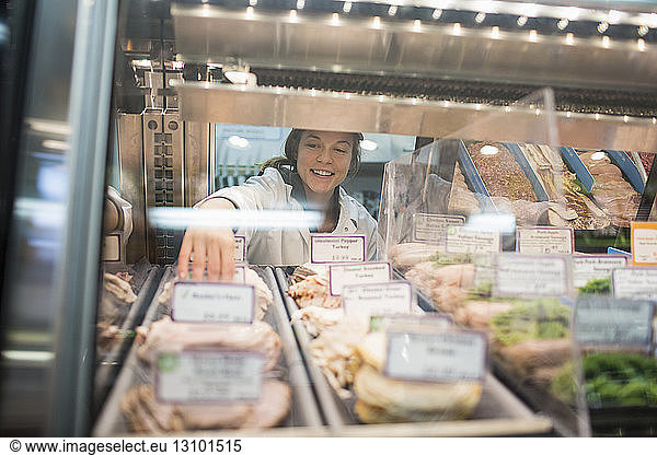 Female worker arranging food in display cabinet at supermarket