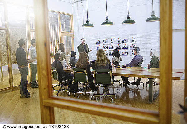 Business people in meeting at board room seen through glass