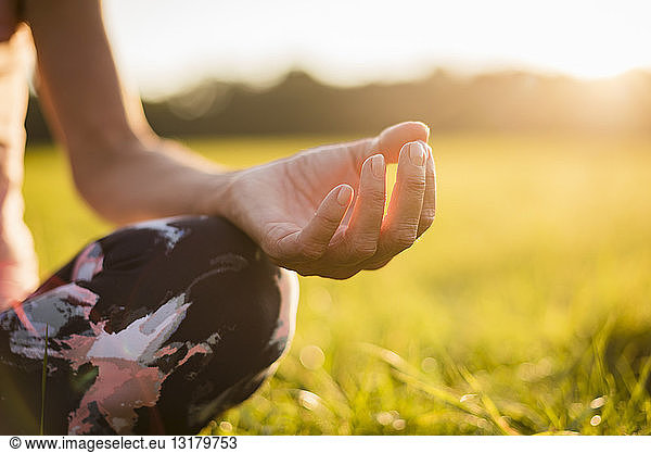 Detail of woman in lotus position on rural meadow at sunset