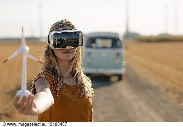 Young woman with VR glasses at camper van in rural landscape holding wind turbine model