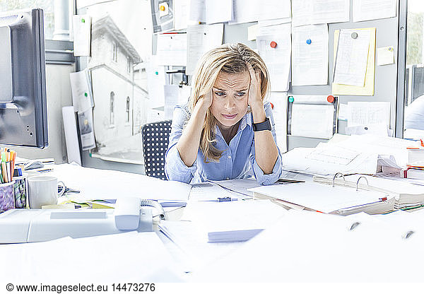 Despaired woman sitting at desk in office surrounded by paperwork
