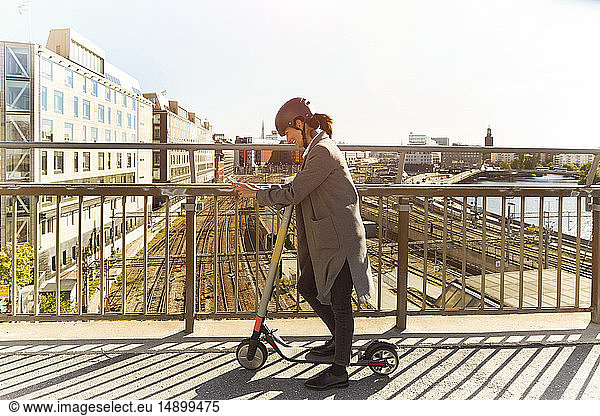Full length side view of mature woman using smart phone while standing with electric push scooter on bridge in city